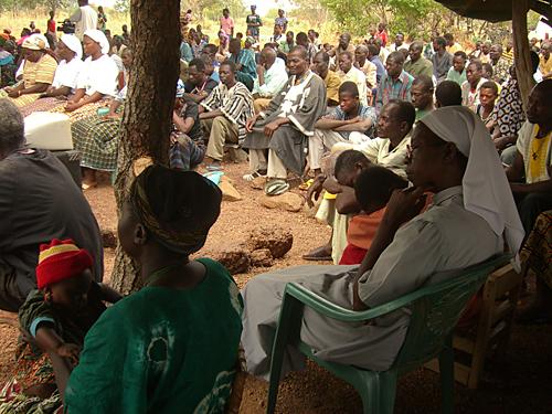 """Fidèles catholique assis sur des pierres lors d'une messe dominicale dans une Eglise en """"plein air"""" du village de Zambo, Burkina Faso"""